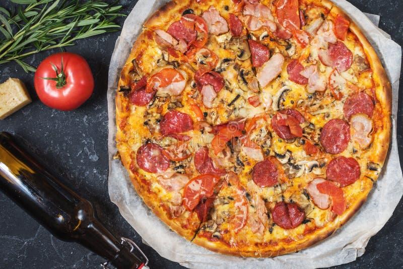 Ny hemlagad pizza med peperonin, skinka, ost och flaskan av öl på lantlig stenbakgrund royaltyfri bild