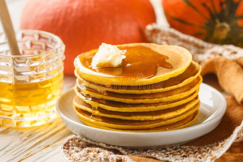 Ny hemlagad pumpapannkaka med honung och smör i en vit platta arkivbild