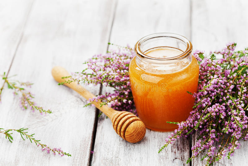 Ny honung i kruka eller krus och blommaljung på trätappningtabellen Kopiera utrymme för text royaltyfria foton