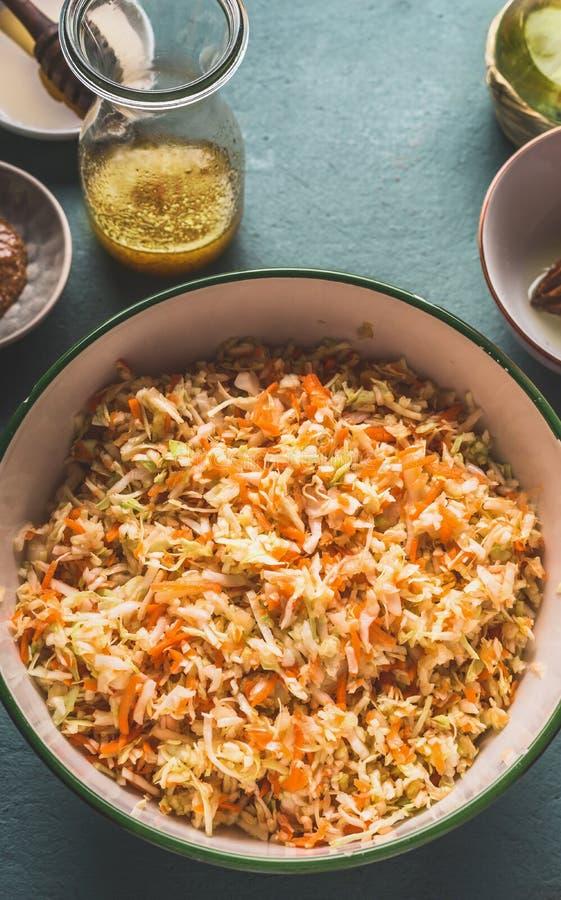 Ny huggen av morotkålsallad med oljadressingen i bunke på köksbordbakgrund, bästa sikt, med kopieringsutrymme vegetarian royaltyfri foto