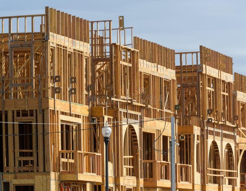 Ny hyreshus under konstruktion på solig dag på bakgrund för blå himmel arkivfoto