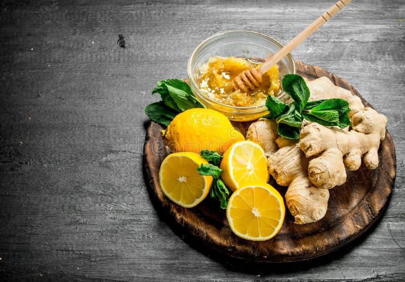 Ny ingefära med honung och citroner på brädet arkivbild