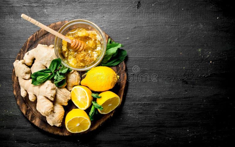 Ny ingefära med honung och citroner på brädet arkivfoto
