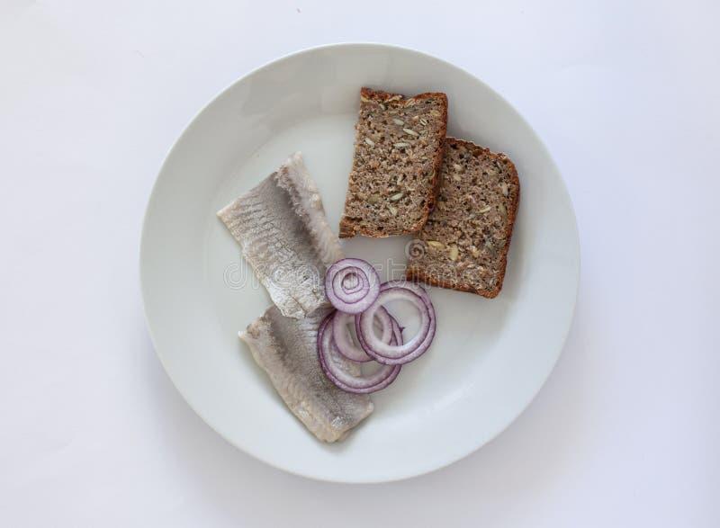 Ny inlagd sill på en platta med homebaked lantliga kärnade ur rågbröd och lökcirklar Skandinavisk mat B?sta sikt p? vit arkivfoton