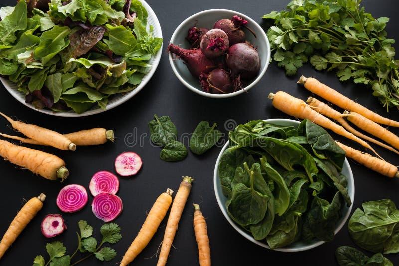 Ny jordbruksprodukter från den lokala lantgården som visas på en svart bakgrund arkivfoton