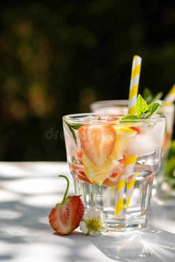 ny jordgubbe för coctail Ny sommarcoctail med jordgubbe- och iskuber Exponeringsglas av jordgubbesodavattendrinken på mörker arkivfoton