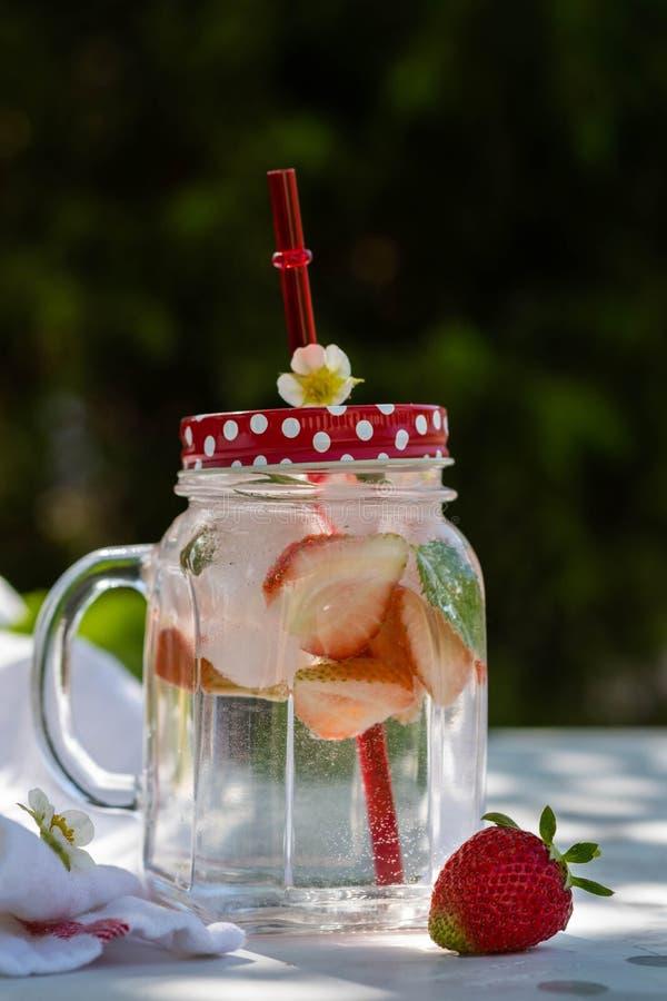 ny jordgubbe för coctail Ny sommarcoctail med jordgubbe- och iskuber Exponeringsglas av jordgubbesodavattendrinken på mörker royaltyfria bilder