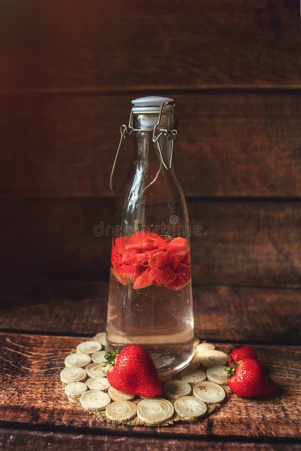 Ny jordgubbe i flaska med vatten, lemonad, vitaminedrink, ecodeco som tonas royaltyfri fotografi