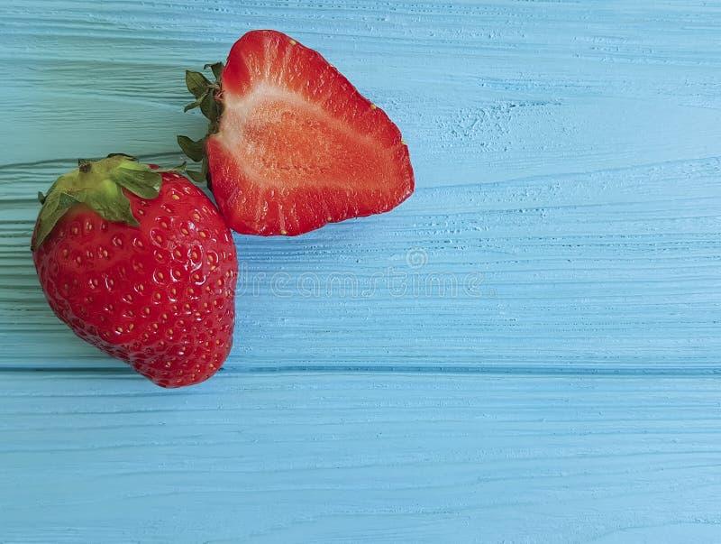 Ny jordgubbe som bantar naturlig tabellmat som är mogen på en blå träbakgrund arkivbild