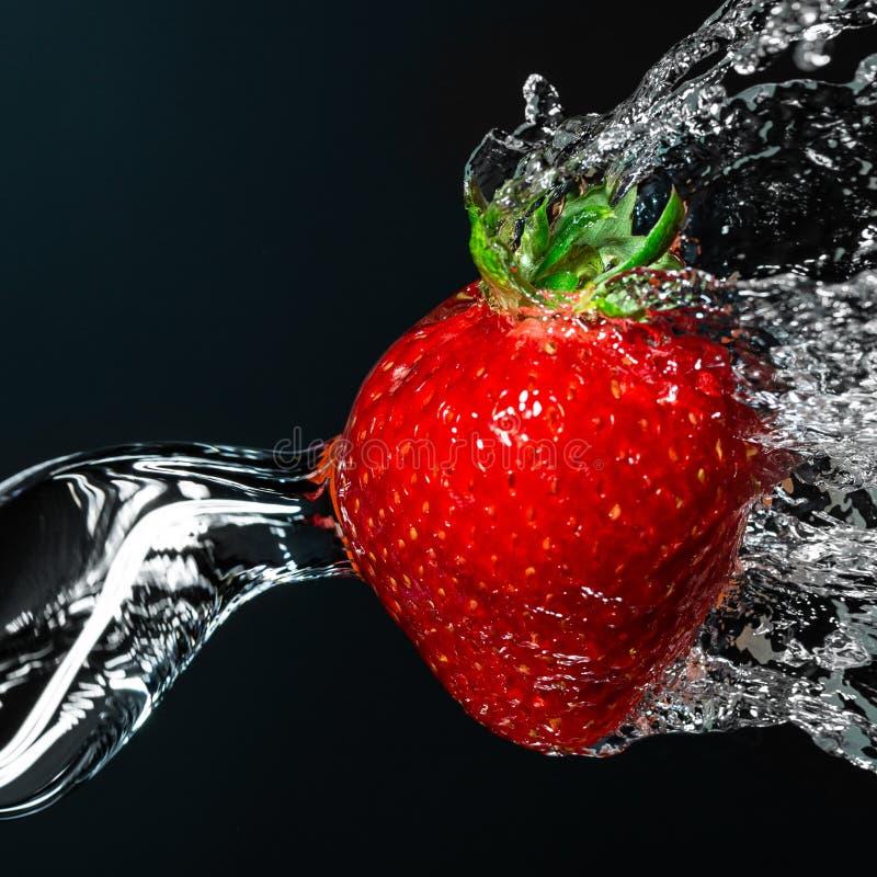 Ny jordgubbebärnärbild under rinnande vatten Stranda av h?r v?nder mot in arkivbild