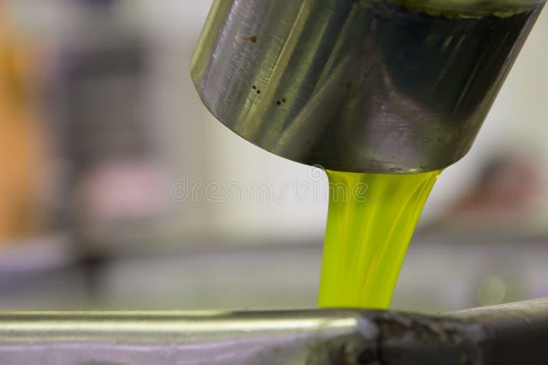 Ny jungfrulig olivolja som häller in i behållare på enpress fabrik efter den olivgröna plockningen, Kreta, Grekland arkivbilder