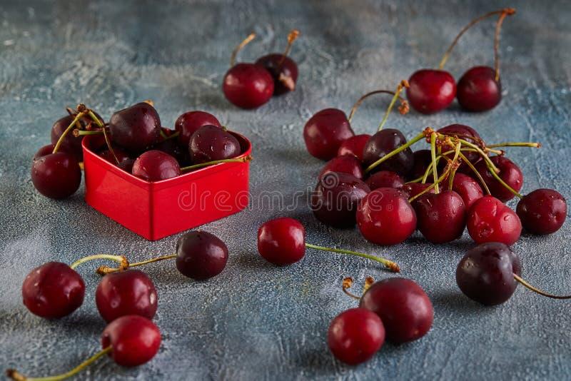 Ny körsbärsröd eller söt körsbär med vattendroppar med en röd hjärta vita isolerade valentiner f?r begrepp dag arkivbild