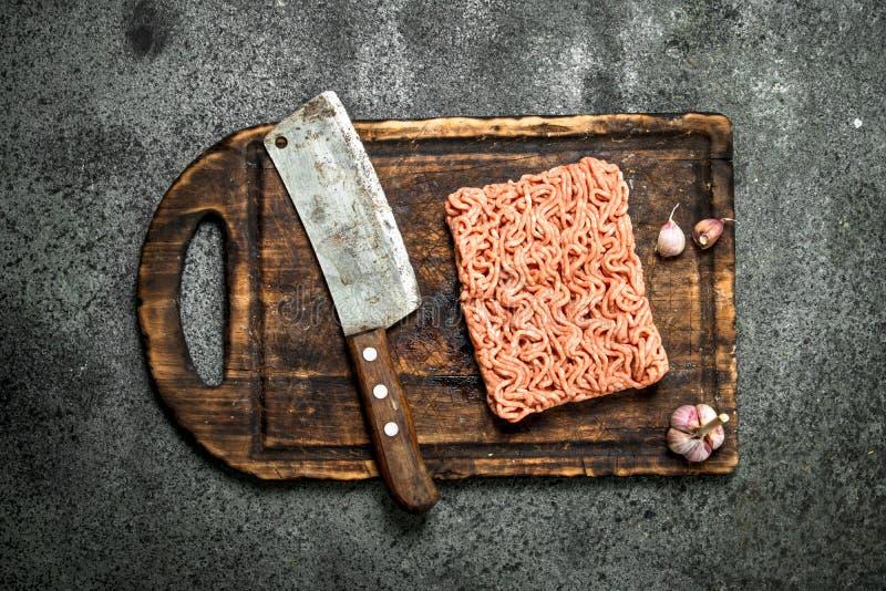 Ny köttfärs med en gammal handyxa och vitlök på en skärbräda fotografering för bildbyråer