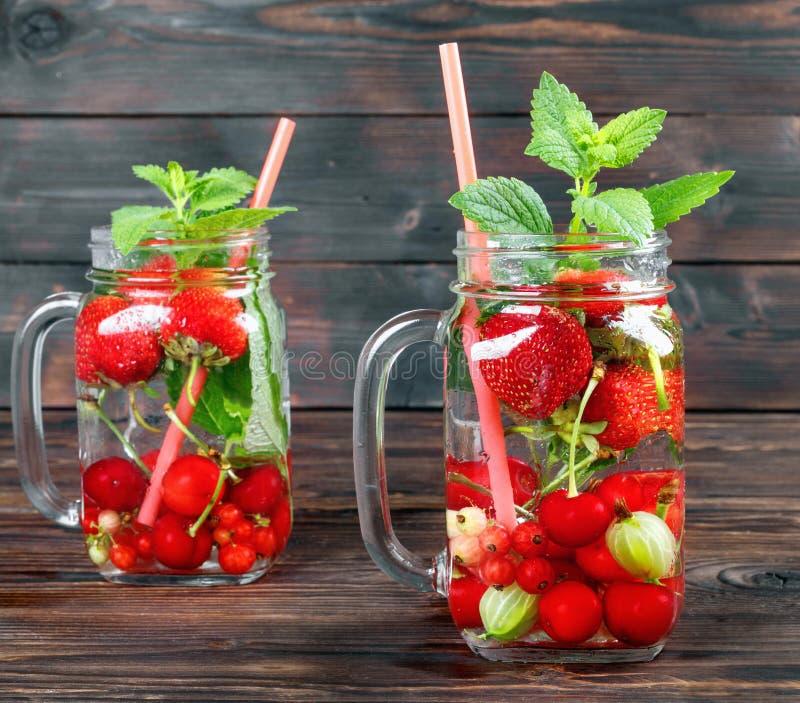 Ny kall drink av mogna saftiga körsbär-, jordgubbe-, vinbär- och krusbärbär royaltyfri fotografi