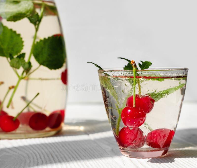 Ny kall drink av mogna saftiga körsbärsröda bär på tabellen arkivfoto
