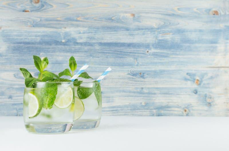 Ny kall sommardryck med limefrukt, bladmintkaramell, sugrör, iskuber på ljus - blå träbakgrund royaltyfri fotografi