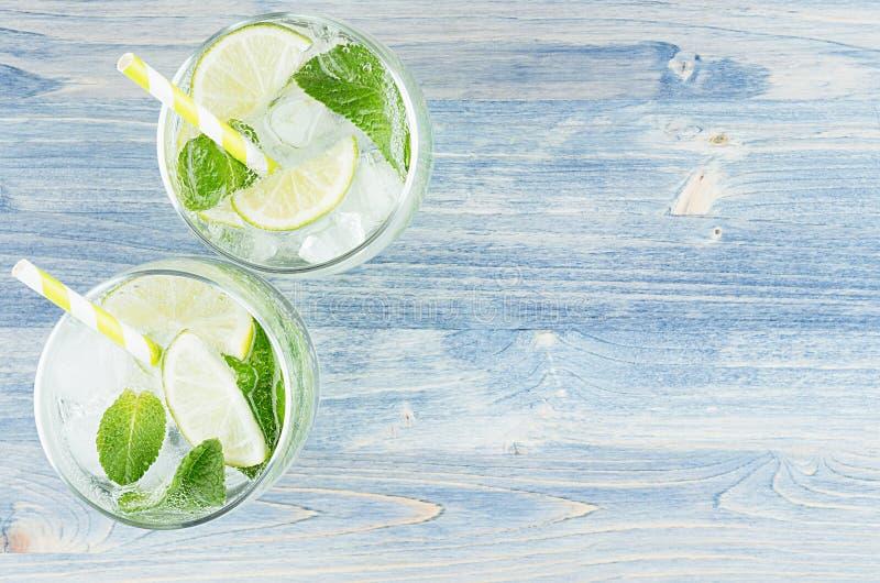 Ny kall sommardryckmojito med limefrukt, bladmintkaramell, sugrör, iskuber, sodavatten på blå wood bakgrund, bästa sikt, gräns royaltyfria bilder