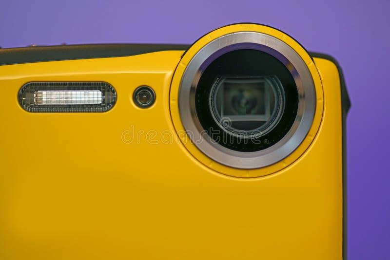 Ny kamera på purpurfärgad bakgrund royaltyfri fotografi