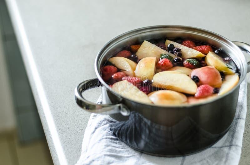 Ny kokt äpplekompot med bär i kruka på kökshandduken, drink för ny frukt, polsk sommardryck arkivbild