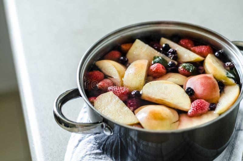 Ny kokt äpplekompot med blåbär och björnbär, i kruka på kökshandduken, drink för ny frukt, sommardryck arkivbilder