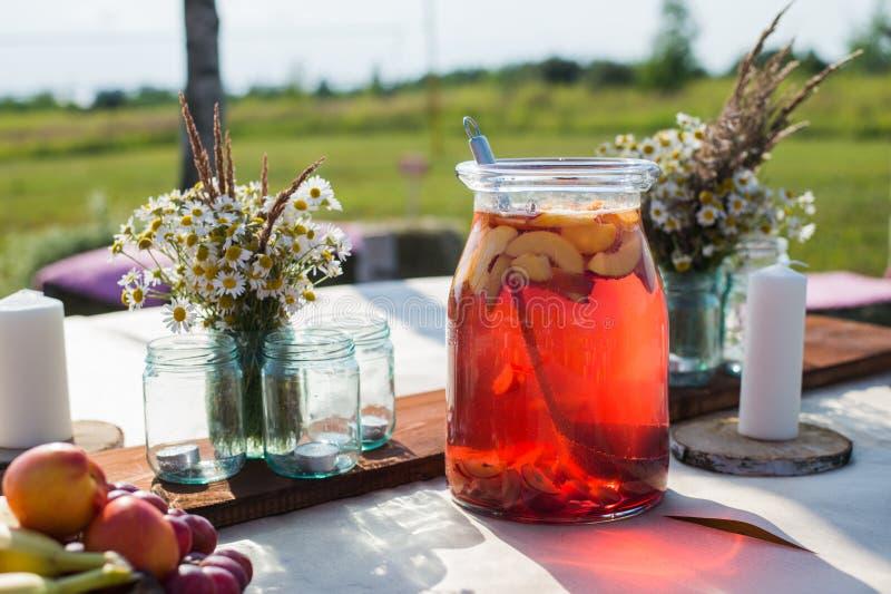 Ny kompott, bär frukt, stearinljus och blommor på trätabellcloseupen Selektivt fokusera Härlig garnering i bohostil arkivfoto