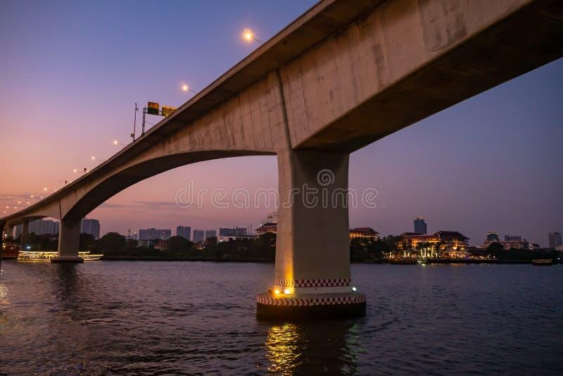 Ny konkret bro över floden med cityscapeplats på skymninghimmelbakgrund royaltyfria bilder