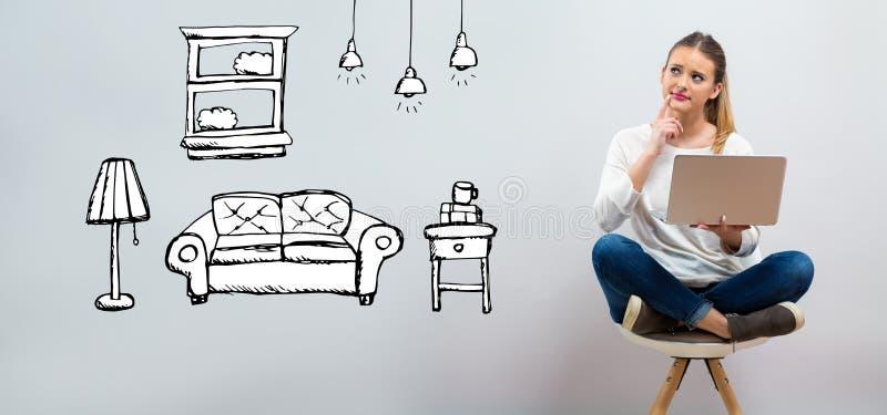 Ny lägenhetdröm med den unga kvinnan som använder hennes bärbar dator royaltyfri bild
