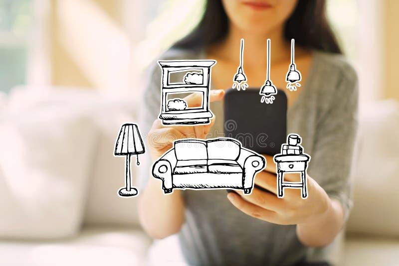 Ny lägenhetdröm med kvinnan som använder en smartphone royaltyfri bild