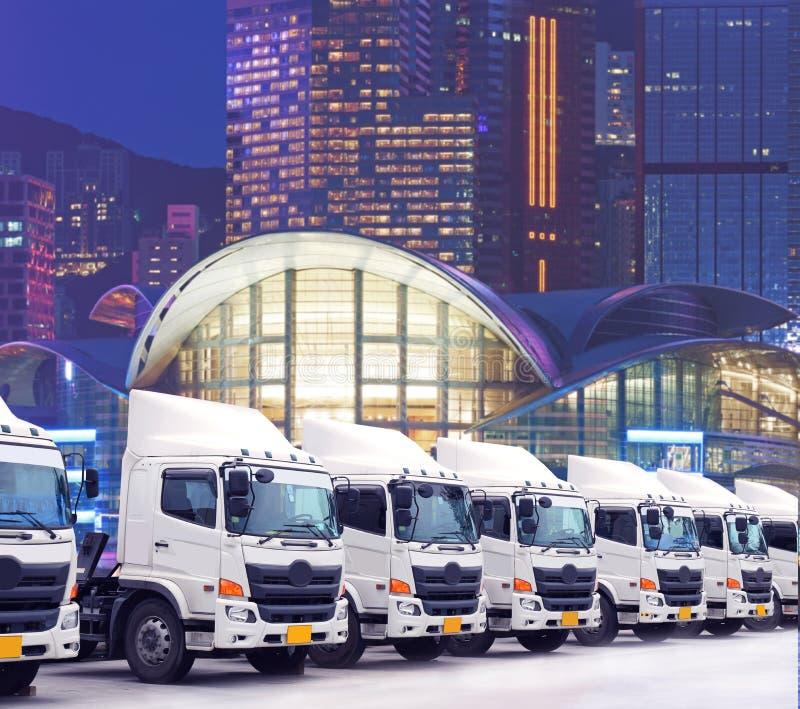 Ny lastbilflotta parkerar framme av storstaden i affärsområde som för trans. royaltyfria foton
