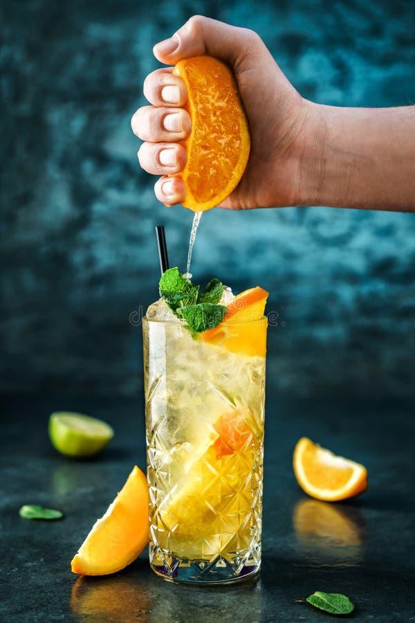 Ny lemonad med mintkaramellen, ingefäran, apelsinen och is i exponeringsglaskrus på det mörkt - blå bakgrund royaltyfria foton