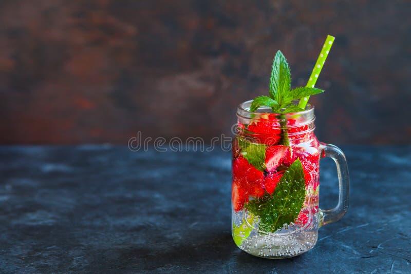 Ny lemonad med mintkaramellen, sommarfrukter och bär i murarekrus arkivfoto