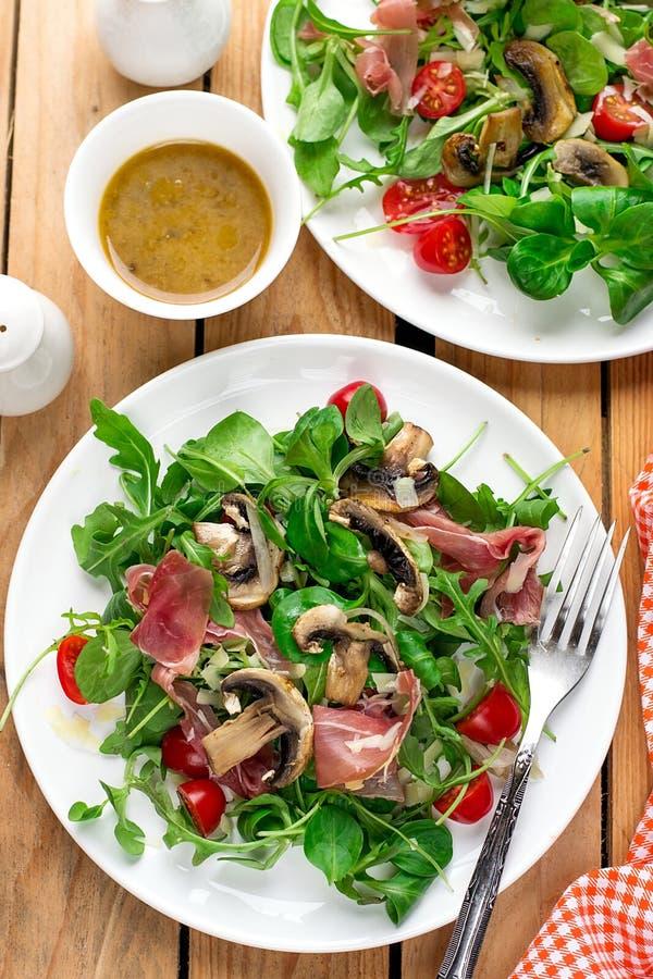 Ny ljus grönsaksallad med arugulagrönsallat, champinjoner, den körsbärsröda tomaten och kurerad skinka royaltyfri fotografi