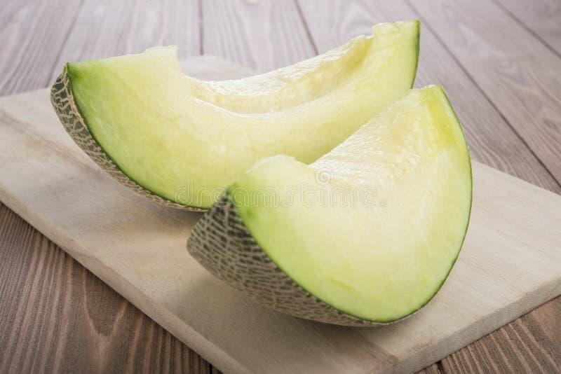 Ny meloncantaloupmelon som skivas på träskärbräda och träbakgrund arkivbild