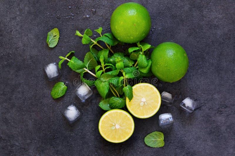 Ny mintkaramell, limefrukt och is på en svart bakgrund Ingrediens för M arkivbild