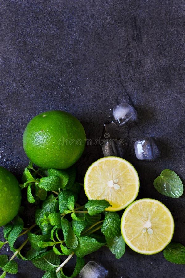 Ny mintkaramell, limefrukt och is på en svart bakgrund Ingrediens för M arkivfoto