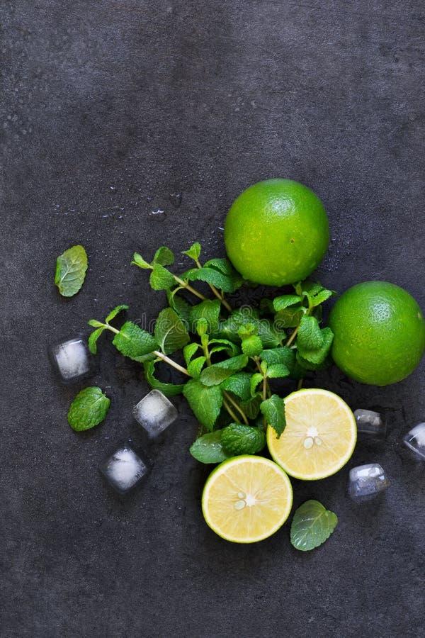 Ny mintkaramell, limefrukt och is på en svart bakgrund Ingrediens för M fotografering för bildbyråer