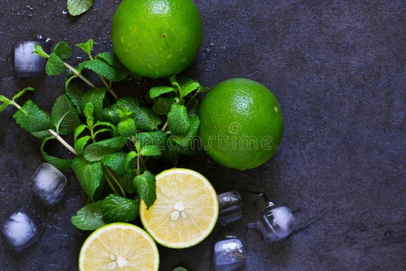 Ny mintkaramell, limefrukt och is på en svart bakgrund Ingrediens för M royaltyfri fotografi