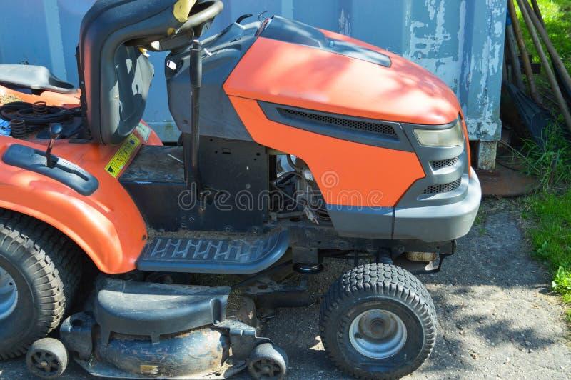 Ny modern röd fyrhjulig gräsklippare för att meja gräs, gräsmatta Jordbruks- utrustning för trädgårdgräsmattaomsorg, motoblock arkivfoton