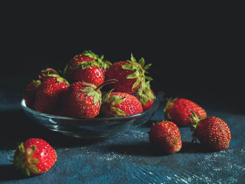 Ny mogen jordgubbe för ful trädgård på ett mörkt - blå bakgrund Verklig organisk mat arkivbild