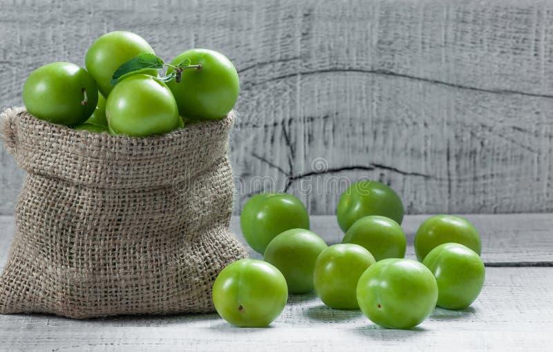 Ny mogen organisk gr?n plommoner eller renklo i s?ckv?vs?ck p? tr?bakgrund arkivbilder