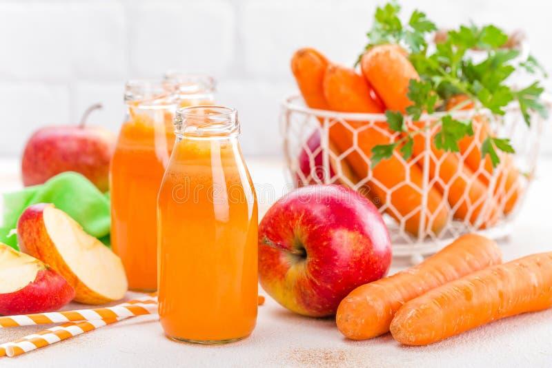 Ny morot och äppelmust på vit bakgrund Morot och äppelmust i glasflaskor på den vita tabellen, closeup fotografering för bildbyråer