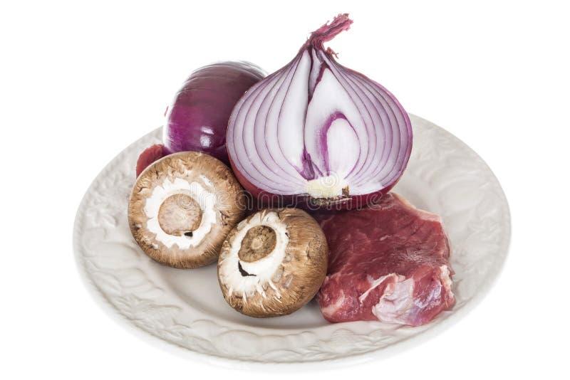 Ny nötköttstek av fransyska som är rå med rå röd lök- och bruntchampinjoner arkivfoto