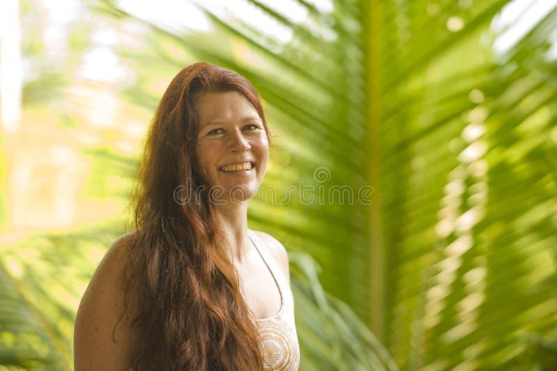 Ny och naturlig st?ende f?r livsstil av den unga h?rliga och lyckliga r?da h?rkvinnan som ler gladlynt och bekymmersl?s tyckande  arkivfoton
