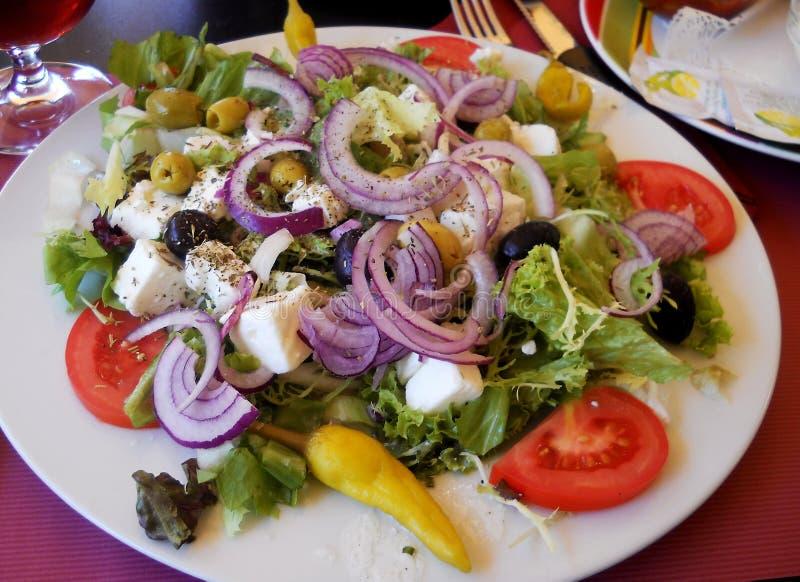 Ny och sund sallad med den röda löken, grönsallat, tomaten, fetaost, oliv och peppar fotografering för bildbyråer