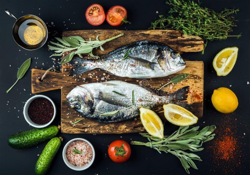 Ny okokt dorado- eller havsbraxenfisk med citronen, örter, olja, grönsaker och kryddor på lantligt träbräde över svart arkivfoton