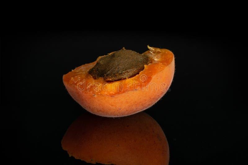 Ny orange aprikos som isoleras på svart exponeringsglas royaltyfri bild