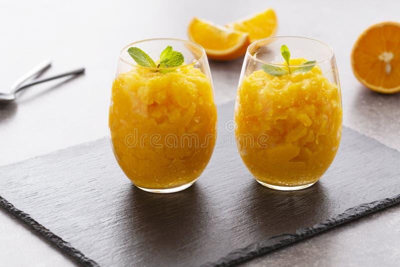 Ny orange citrus sorbet som garneras med mintkaramellen - traditionell kall efterr?tt arkivfoto