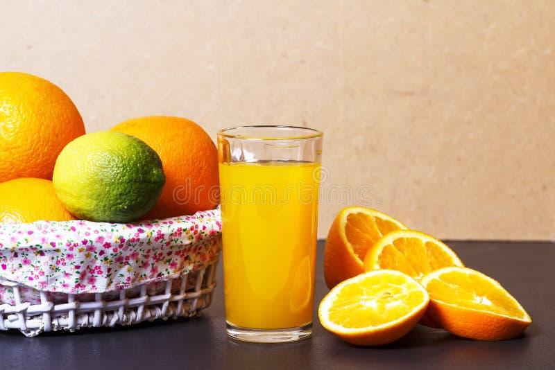 Ny orange fruktsaft i den glass dryckeskärlen och hela apelsiner i korg på en tabell Skivad apelsinskivor och orange fruktsaft royaltyfri foto