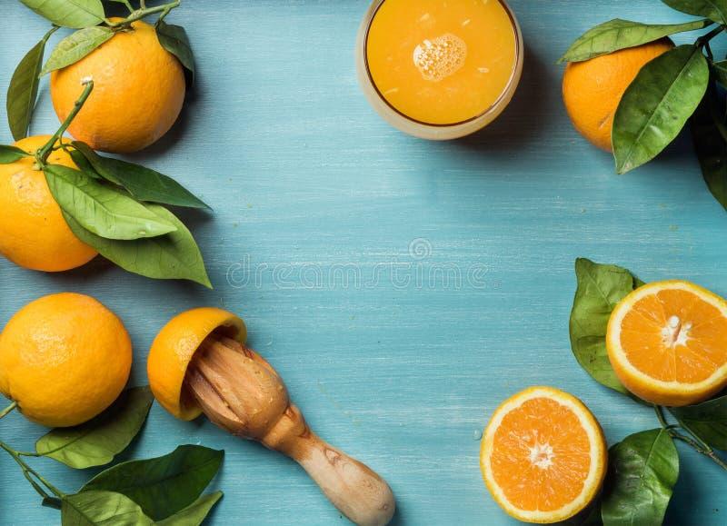 Ny orange fruktsaft i exponeringsglas och apelsiner med sidor på träturkosblått målade bakgrund arkivfoton