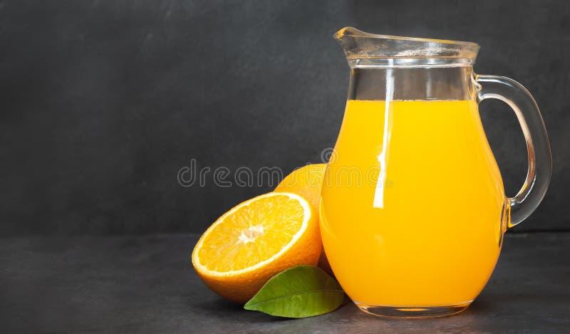 Ny orange fruktsaft i exponeringsglastillbringaren, nya apelsiner på den mörka tabellen arkivfoton